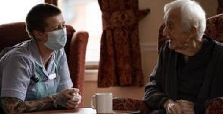 A masked carer talking to an older person