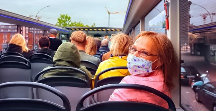 Woman on top deack of open top bus, looking back at us, wearing face mask.