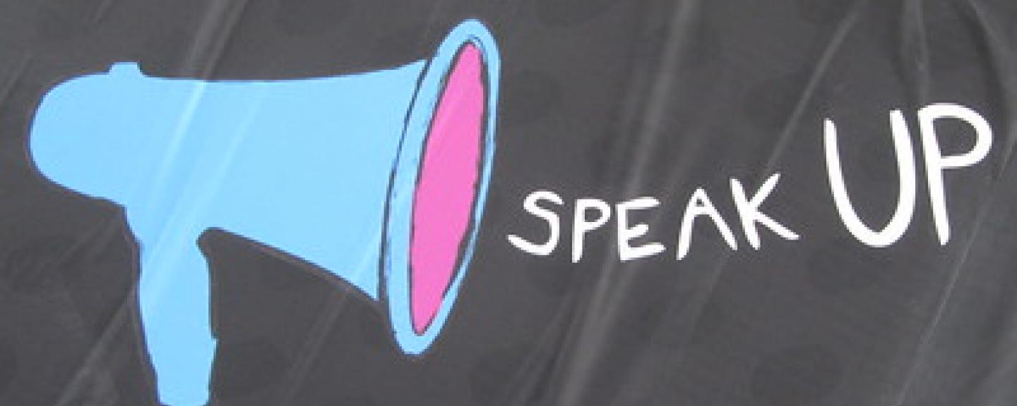 Blue microphone to the left hand side, Speak Up in white writing centrally aligned