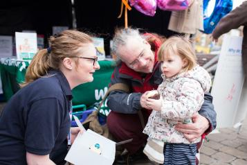 Healthwatch staff member talking to a young child at an event