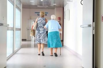 Hospital corridor, Old woman walking arm in arm with a woman, backs to camera