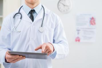 Doctor in white coat holding iPad, Left side of shot, Shoulder/Torso view