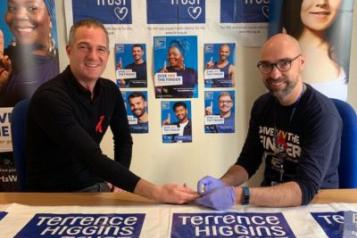 Photogrpah of Hove MP Peter Kyle, HIV Testing, Terrence Higgins Trust Posters IN foreground and Background