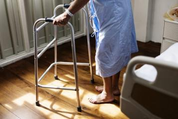 photograph, side view looking to floor, close up of patient holding zimmer frame