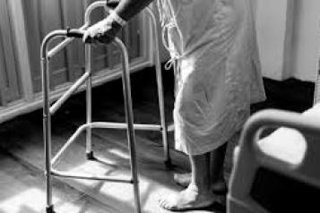 older person using walking frame in hospital