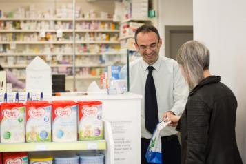 Male pharmacist serving a female customer