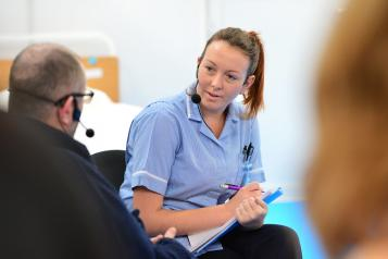 Female nurse, facing towards patient, patient out of focus and at forefront of image