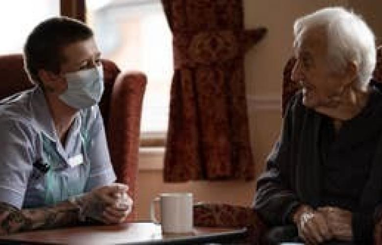 Elderly man and nurse chatting in care home