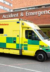 yellow and green ambulance outside a hospital