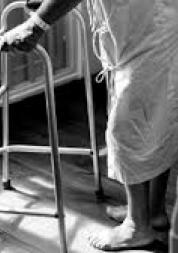 older person using walking frame in hospital