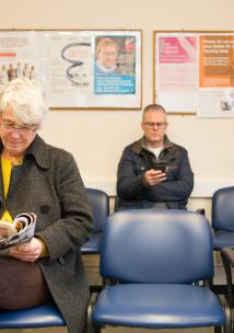 Several people, male and femail, older and younger, in a doctors waiting area.