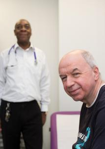 GP Surgery, Man in focus, in foreground to right, Doctor blurred, in background to left