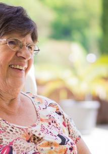 older woman sitting in chair by a garden smiling