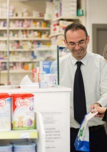 Male pharmacist serving a female customer